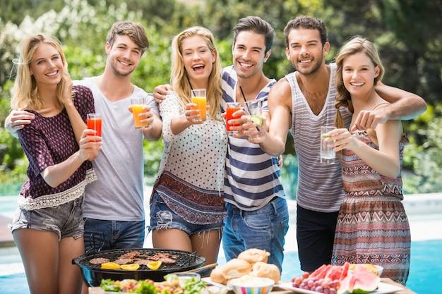 Portret van vrienden die sap hebben bij in openlucht barbecuepartij