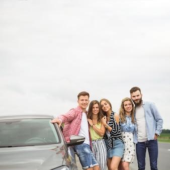 Portret van vrienden die zich dichtbij de geparkeerde auto bevinden