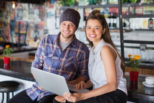 Portret van vrienden met laptop in restaurant