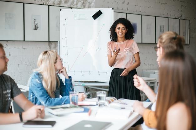 Portret van vrij african american girl permanent in de buurt van bestuur en gelukkig nieuw project bespreken met collega's in kantoor
