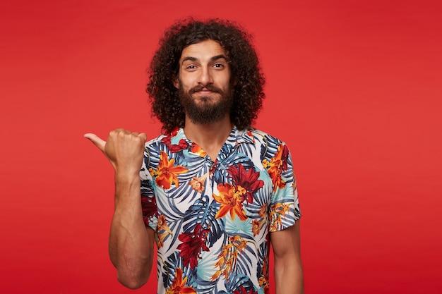 Portret van vrij bebaarde brunette krullende man die lichtjes glimlacht en opzij toont met opgeheven duim, lippen gevouwen houdt, gekleed in gebloemd overhemd