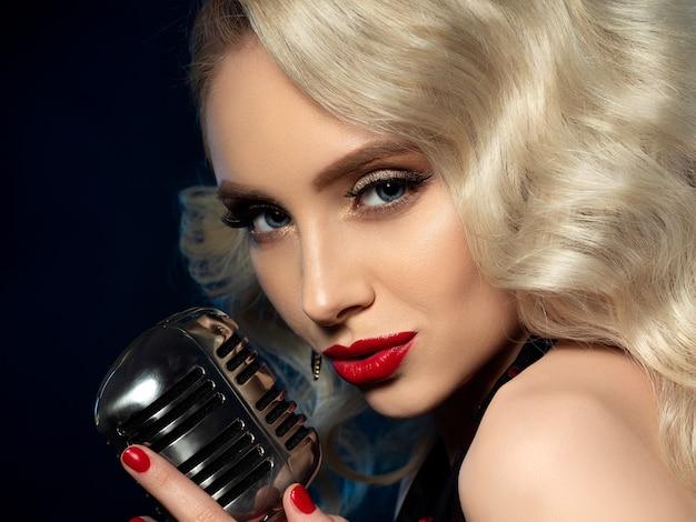 Portret van vrij blonde zangeres met retro gestileerde microfoon. mooie make-up met rode lippen. concert, karaoke, beroemdheid, muziekshow of nachtclubconcept.