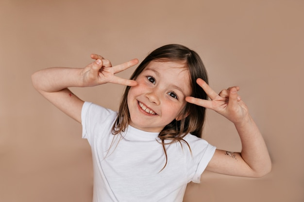 Portret van vrij charmant meisje dat vredestekens dichtbij het gezicht toont en over beige muur glimlacht
