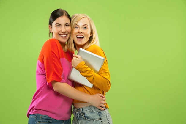 Portret van vrij charmante meisjes in casual outfits geïsoleerd op groen
