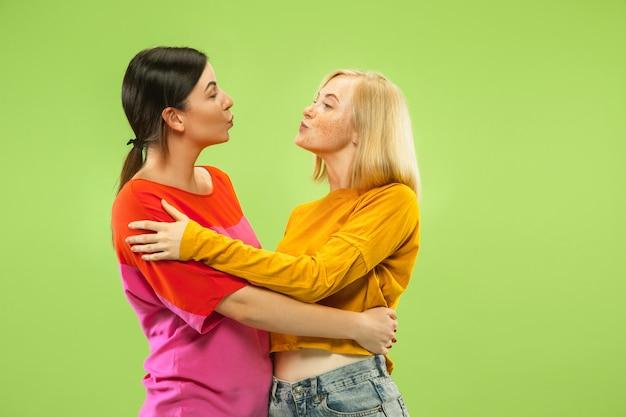 Portret van vrij charmante meisjes in casual outfits geïsoleerd op groene ruimte. twee vrouwelijke modellen als vriendinnen of lesbiennes