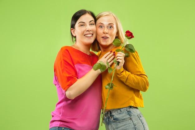 Portret van vrij charmante meisjes in casual outfits geïsoleerd op groene studio achtergrond. twee vrouwelijke modellen als vriendinnen of lesbiennes. concept van lgbt, gelijkheid, menselijke emoties, liefde, relatie.