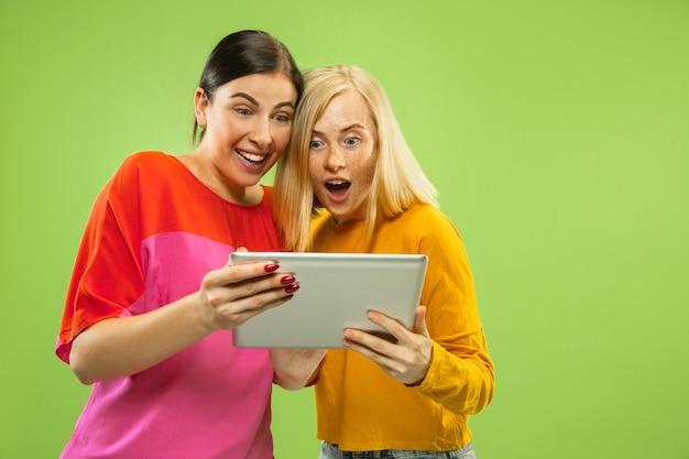 Portret van vrij charmante meisjes in casual outfits geïsoleerd op groene studio achtergrond. vriendinnen of lesbiennes die een tablet gebruiken voor de lol of voor betalingen. concept van lgbt, menselijke emoties, liefde, relatie.