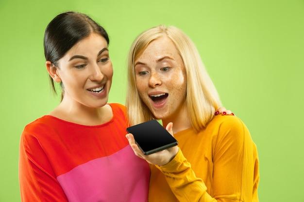 Portret van vrij charmante meisjes in casual outfits geïsoleerd op groene studio achtergrond. vriendinnen of lesbiennes praten over smartphone. concept van lgbt, gelijkheid, menselijke emoties, liefde, relatie.