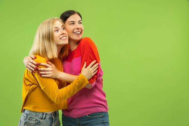Portret van vrij charmante meisjes in casual outfits op groene studio