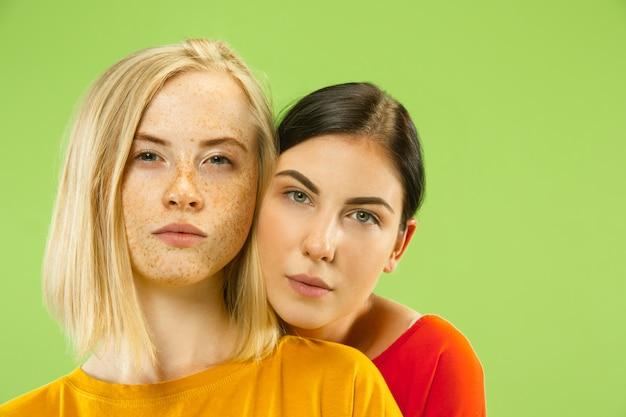 Portret van vrij charmante meisjes in geïsoleerde casual outfits. twee vrouwelijke modellen als vriendinnen of lesbiennes. concept van lgbt, gelijkheid, menselijke emoties, liefde, relatie.