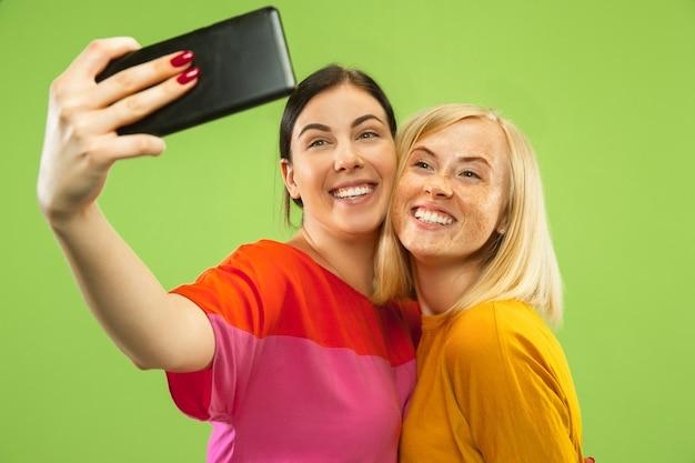 Portret van vrij charmante meisjes in geïsoleerde casual outfits. vriendinnen of lesbiennes selfie maken. concept van lgbt, gelijkheid, menselijke emoties, liefde, relatie.