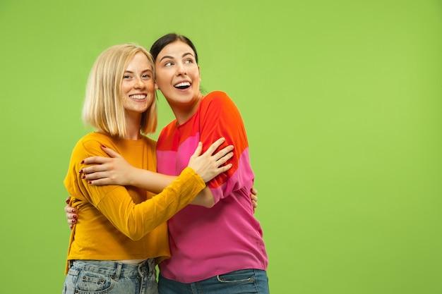 Portret van vrij charmante meisjes in vrijetijdskleding die op groene studiomuur wordt geïsoleerd