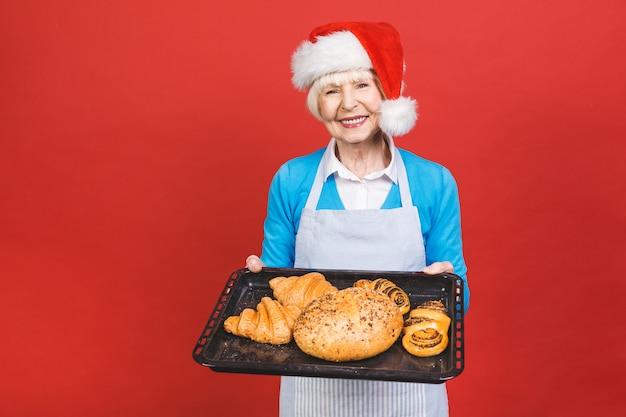 Portret van vrij charmante vrolijke oude vrouw met rimpel met gebaren zoete zelfgemaakte bakkerijproducten