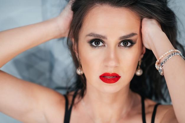 Portret van vrij donkerbruin meisje met rode lippen op blauwe achtergrond close-up