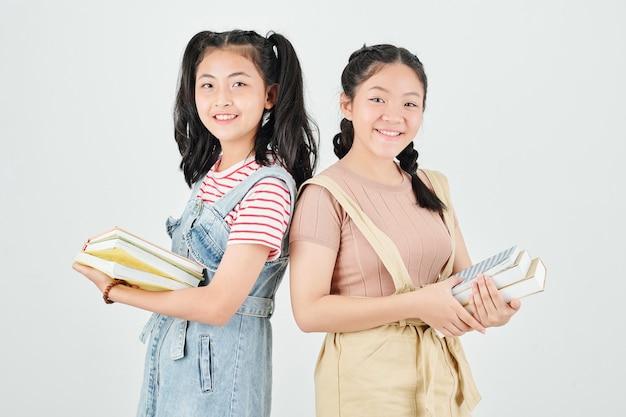 Portret van vrij glimlachende aziatische schoolmeisjes met boeken die zich rijtjes bevinden en kijken