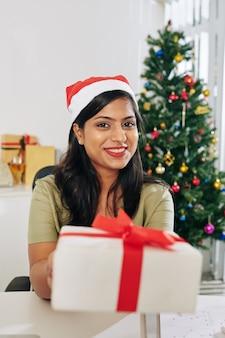 Portret van vrij glimlachende jonge indische onderneemster in de uitgestrekte handen van de kerstmanhoed met aanwezige kerstmis