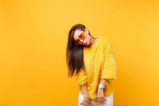 Portret van vrij grappige jonge vrouw in bont trui witte broek hart oranje bril waait lippen geïsoleerd op heldere gele achtergrond. mensen oprechte emoties, lifestyle concept. reclame gebied.