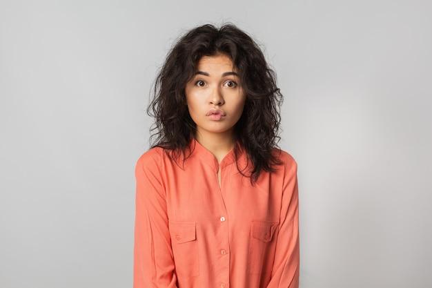 Portret van vrij grappige vrouw met geschokte uitdrukking van gezicht, krullend haar, natuurlijke make-up, jonge hipster, verrast emotie, geïsoleerde, oranje blouse