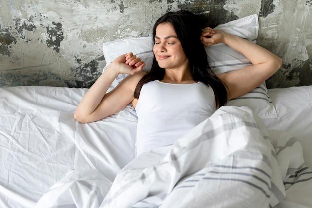 Portret van vrij het jonge vrouw ontspannen in bed