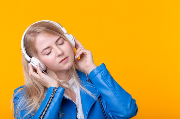 Portret van vrij jong meisje blonde vrouwelijke student bedrijf smartphone met blauwe lederen jas koptelefoon poseren op een gele achtergrond.