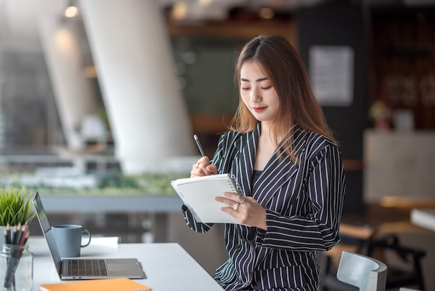 Portret van vrij jonge aziatische onderneemster die nota neemt en laptop computer gebruikt op kantoor modern