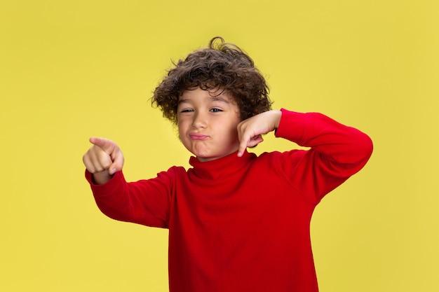 Portret van vrij jonge krullende jongen in rode slijtage op gele studioachtergrond. jeugd, expressie, onderwijs, leuk concept.