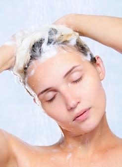 Portret van vrij jonge vrouw die haar haar wast