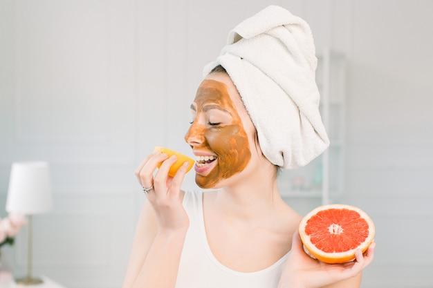 Portret van vrij jonge vrouw met kleimasker op haar gezicht met plakjes citroen en grapefruit, gezichtsverzorging