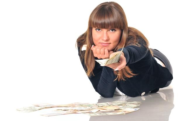 Portret van vrij kaukasische witte donkerbruine vrouw die dichtbij euro- en dollarbiljetten ligt.