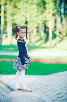 Portret van vrij klein kind meisje permanent buiten in zomer park gelukkig lachend met twee paardenstaarten op haar hoofd met gestrekte haarbanden