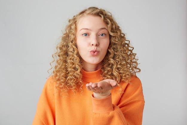 Portret van vrij krullend meisje die luchtkus met steenbolklippen en gesloten ogen verzenden die op witte muur worden geïsoleerd