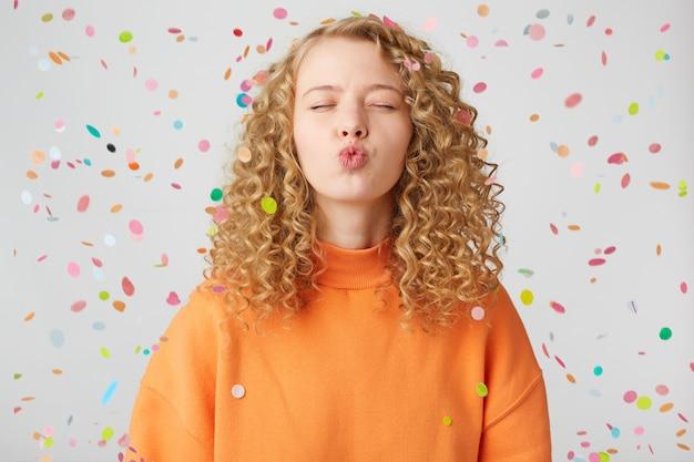 Portret van vrij krullend meisje in oranje trui met blazende lucht kus met pruillip lippen en gesloten ogen staat onder vallende confetti