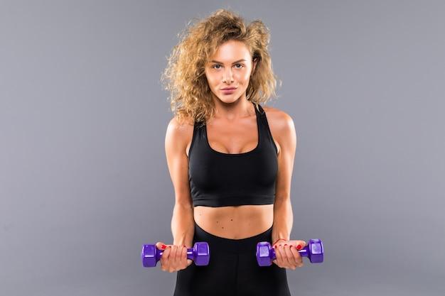 Portret van vrij krullend sportief meisje met gewichten dumbbels geïsoleerd op een grijze muur