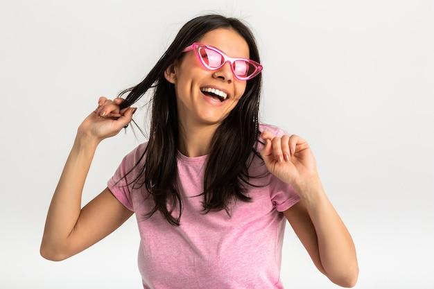 Portret van vrij lachende emotionele vrouw in roze shirt en stijlvolle zonnebril, witte tanden, positief poseren geïsoleerd