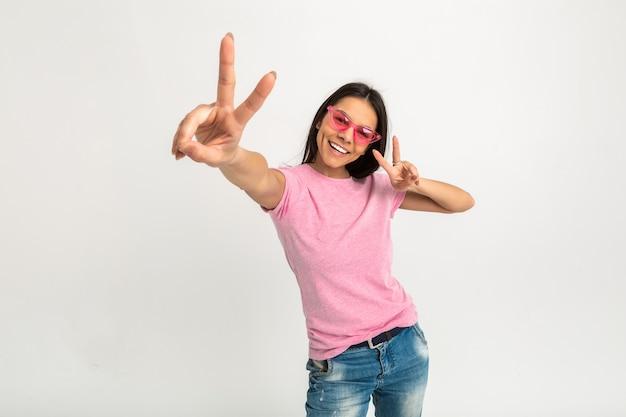 Portret van vrij lachende emotionele vrouw in roze shirt en zonnebril met haar armen naar voren