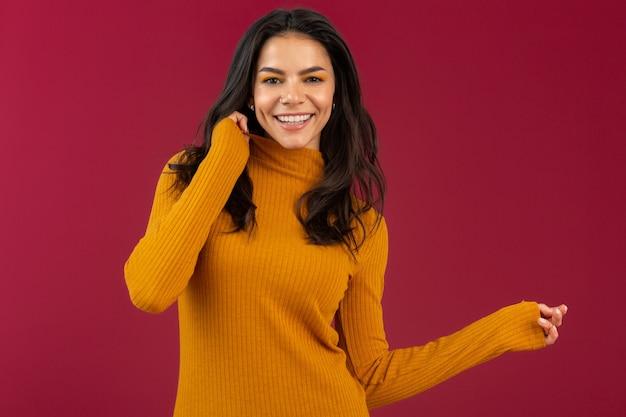 Portret van vrij lachende stijlvolle brunette spaanse vrouw in gele herfst winter mode jurk trui poseren geïsoleerd op rode muur