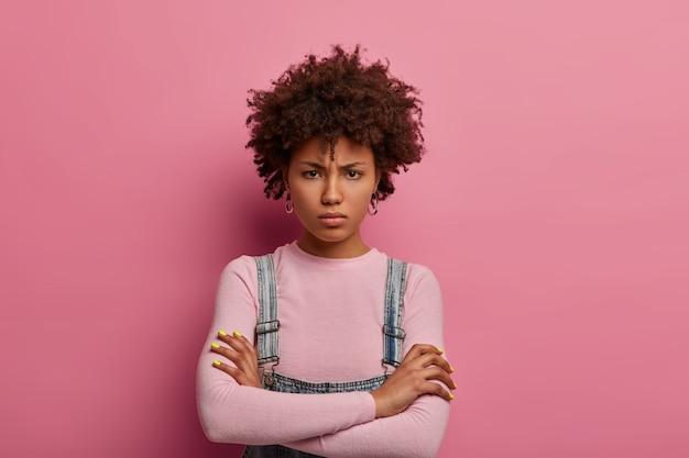 Portret van vrij mokkend jonge vrouw staat ontevreden, houdt de handen gekruist, wordt beledigd door iemand en wacht op excuses, kijkt van onder voorhoofd, poseert boos tegen roze muur