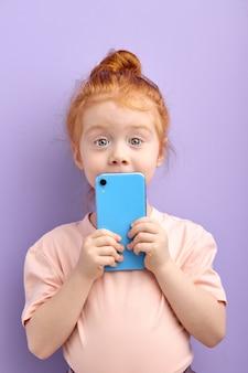 Portret van vrij roodharig kindmeisje dat smartphone gebruikt die op paars wordt geïsoleerd