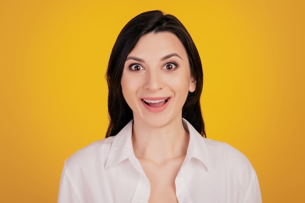 Portret van vrij schattig meisje opgewonden gezicht kijkt camera op gele achtergrond