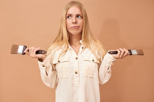 Portret van vrij tienermeisje met beugels en lang haar met behulp van speciaal gereedschap tijdens het schilderen van binnenmuren om ze te beschermen tegen schade door water of corrosie