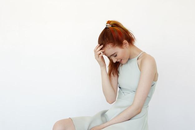 Portret van vrij verlegen roodharige meisje met gekleurde strengen in haar in paardenstaart gekleed in lichtblauwe jurk met gelukkige en vrolijke blik poseren de eerste keer. jeugd, schoonheid en mode-concept