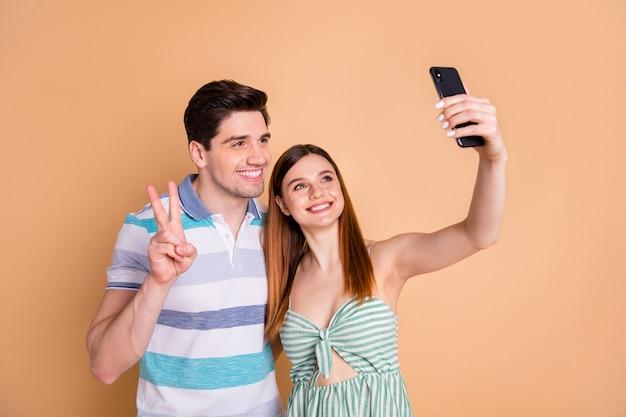 Portret van vrij vrolijke paarvrienden die selfie maken met v-teken