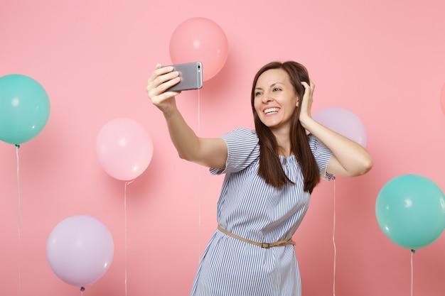 Portret van vrij vrolijke vrouw in blauwe jurk die selfie op mobiele telefoon doet en hand in de buurt van hoofd houdt op roze achtergrond met kleurrijke luchtballonnen. verjaardag vakantie partij mensen oprechte emoties concept.