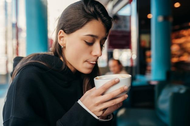 Portret van vrij vrouwelijke koffie drinken close-up. dame die een witte mok met hand houdt.