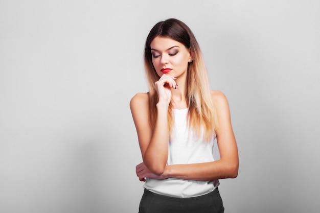 Portret van vrij zeker nadenkende vrouw die zich over grijze muur met exemplaarruimte bevindt