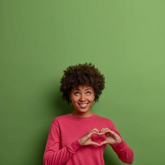 Portret van vrolijk, aangenaam ogende afro-amerikaanse vrouw hartteken over borst vertoont, liefde en zorg uitdrukt, kijkt boven, draagt roze trui, vormt tegen groene muur, lege ruimte naar boven