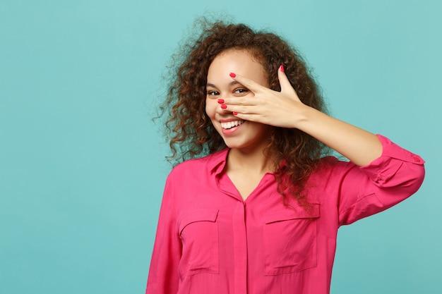 Portret van vrolijk afrikaans meisje in roze casual kleding die gezicht bedekt met hand geïsoleerd op blauwe turquoise muur achtergrond in studio. mensen oprechte emoties, lifestyle concept. bespotten kopie ruimte.