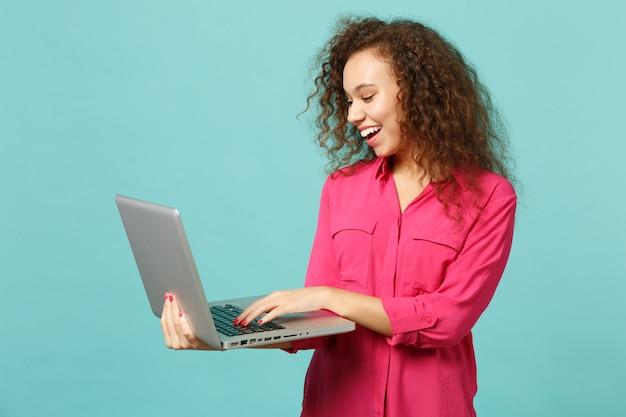 Portret van vrolijk afrikaans meisje in roze casual kleding met behulp van laptop pc-computer geïsoleerd op blauwe turquoise muur achtergrond in studio. mensen oprechte emoties, lifestyle concept. bespotten kopie ruimte.
