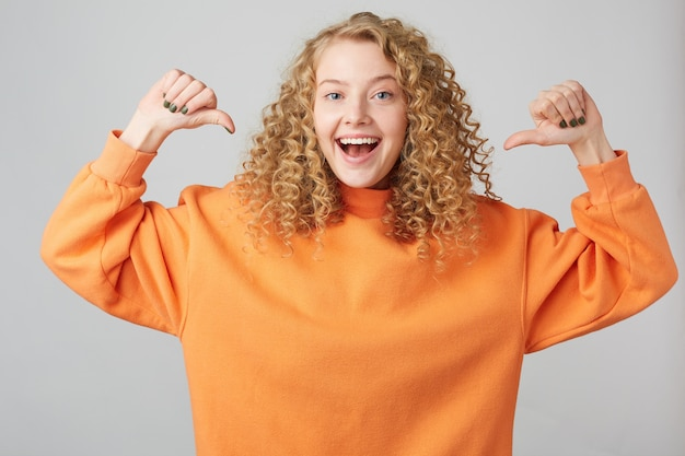 Portret van vrolijk blond meisje in basiskleding glimlachend en balde vuisten als winnaar met duimen op haar gericht