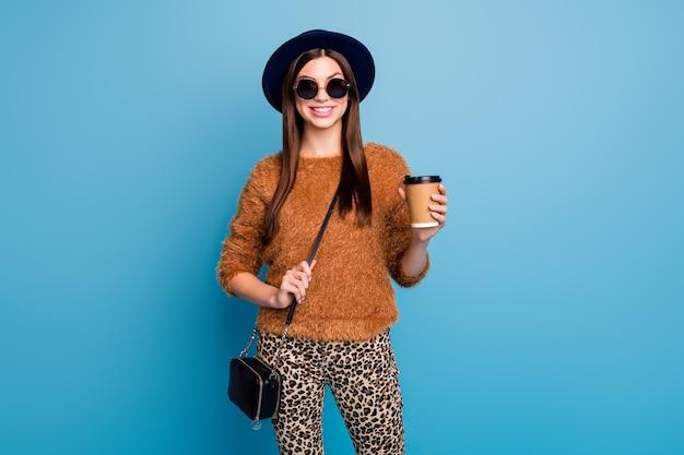 Portret van vrolijk emoties meisje hebben herfst lente vakantie houden papieren kaart kopje koffie drank latte genieten dragen handtas goed kijken bruine kleding geïsoleerde blauwe kleur muur
